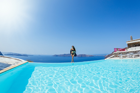 Young, beautiful woman standing on the edge of the pool with a drink in her hand on the background of the sea.
