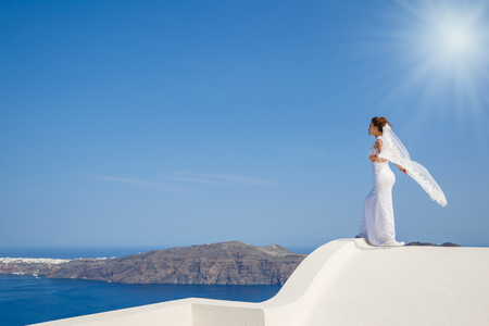 Beautiful bride stands on a high roof over the sea against the sky and the sea of Santorini, Greece