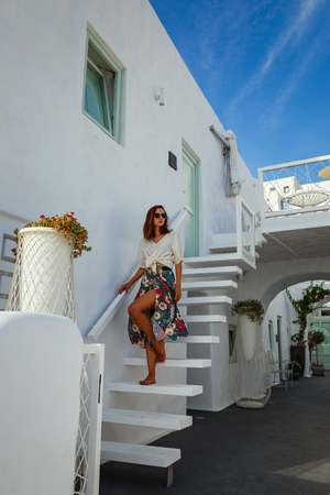 Young beautiful woman on the background a Greek house with stairs Stock Photo