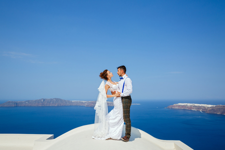 Beautiful couple standing on the roof high above the sea on the background of sky and sea in Santorini, Greece Banco de Imagens - 121183434