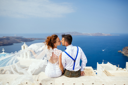 Bride and groom sit together and kiss on the background of the sea, Santorini island, Greece