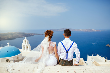 Bride and groom sit together and look at the sea, Santorini island, Greece