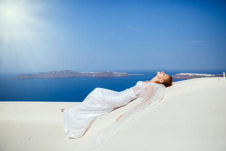 Bride in white dress tans against the background of the sea, the island of Santorini