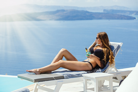 Young, beautiful woman lying by the pool with a drink in her hand on the background of the sea