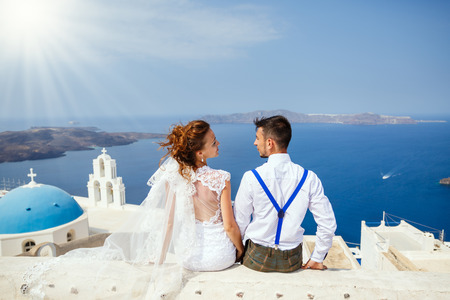 Groom and the bride sit side by side on the background of the sea, the island of Santorini, Greece