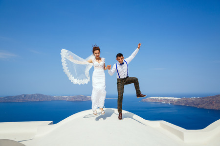 Bride and groom together, jump high on a background of the sea