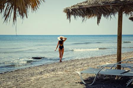 Young woman walking on the beach, Greece, Santorini
