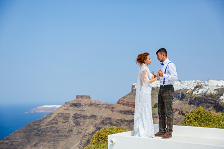 Bride and groom stand next to the sea, Santorini island, Greece