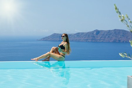 Young woman sitting on the edge of the pool, back to the sea and drinking a cocktail