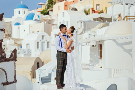 Young couple against the sea and architecture, Santorini Greece Stock Photo
