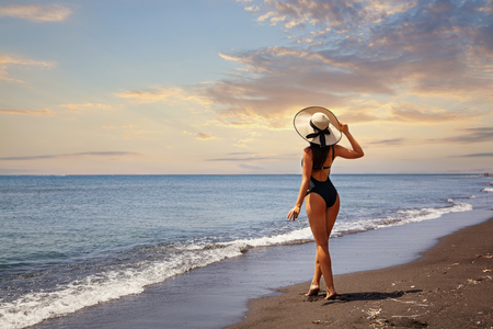 Young woman on the beach watching the sunset Stock Photo