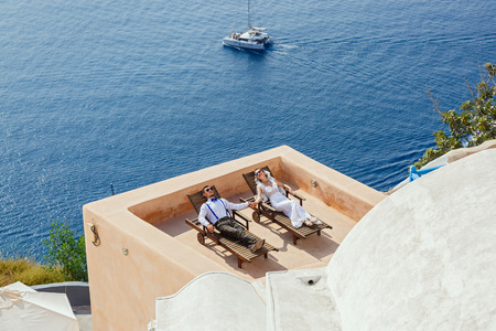 Bride and groom lie next to each other on the balcony and sunbathe Stock Photo