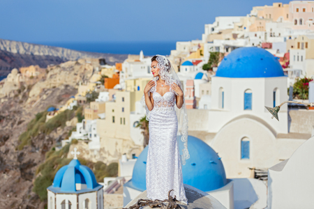 Young bride on the background of sea and architecture, Santorini island, Greece