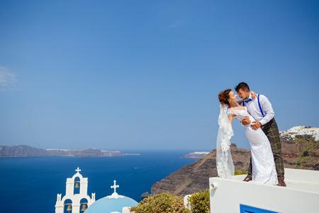 Bride and groom dancing on the roof of Santorini island, Greece