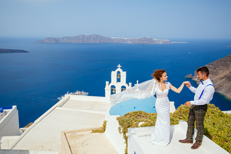 Beautiful bride stands on a high roof over the sea against the sea of Santorini, Greece
