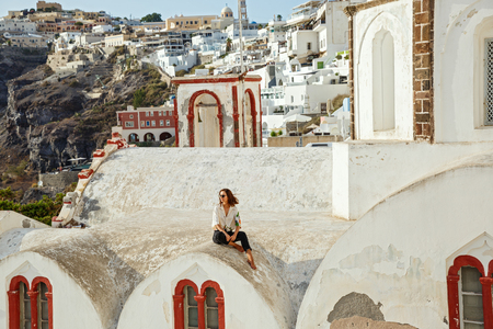 Young woman on the high tower of Santorini architecture