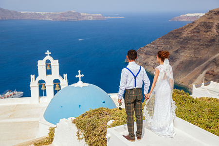 Bride and groom stand next to the sea, Santorini island, Greece