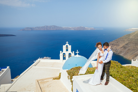 Bride and groom dancing on the roof of Santorini island, Greece