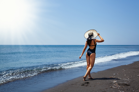 Young woman walking on the beach, Greece, Santorini