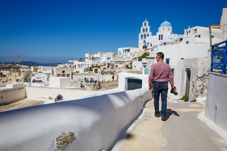 Man traveler walks and photographs the architecture and landscape of the island of Santorini, Greece Stok Fotoğraf