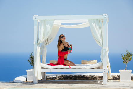 Beautiful young woman in red silk peignoir sunbathing by the pool in the shade of the awning