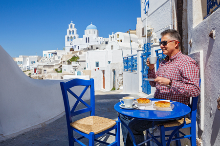 Man has Breakfast and drinks coffee in a cafe on the streets of Santorini.