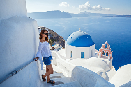 Beautiful young woman in shorts against the white architecture of Santorini Banque d'images