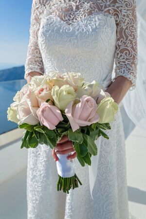 Bride with bouquet on background of sea and sky