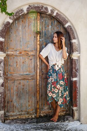 Young beautiful woman standing at the entrance of the house, Greece Stok Fotoğraf