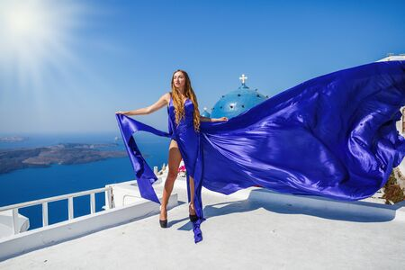 Beautiful woman in a blue dress stands on a high balcony above the sea, Greece, Santorini island.