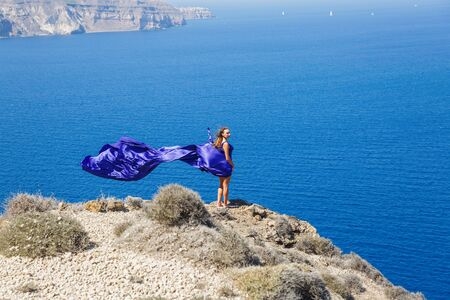 Beautiful woman in a blue dress stands over a cliff and looks at the sea, Greece, Santorini island.