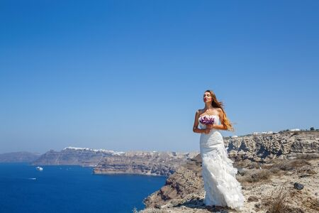 Beautiful woman in a white dress stands over a cliff and looks at the sea, Greece, Santorini island.