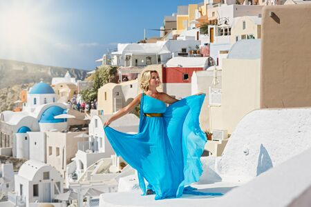 Beautiful woman in dress against  architecture of Santorini island, Greece