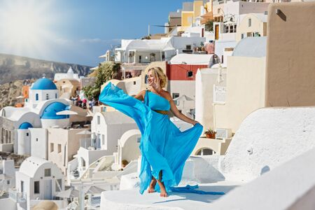 Beautiful woman in dress against architecture of Santorini island, Greece Stok Fotoğraf