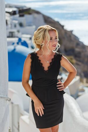 Beautiful woman in dress against the sea and architecture of Santorini island, Greece