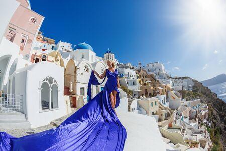 Beautiful woman in dress against  sea and architecture of Santorini island, Greece Stok Fotoğraf