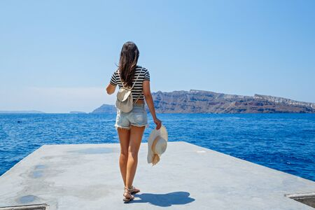 Young woman stands on the pier and looks at the sea Stok Fotoğraf