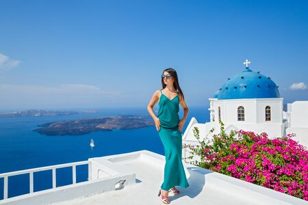 Young woman in a dress standing on the balcony above the sea Stok Fotoğraf
