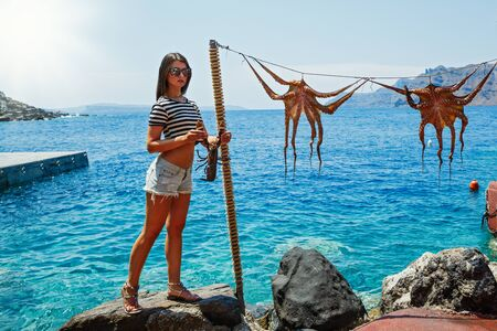 Young woman holds in hands of Omar, on the background of the sea and octopus on a rope