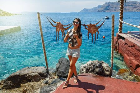 Young woman holds in hands of lobster, on the background of the sea and octopus on a rope Stok Fotoğraf