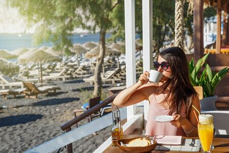 Young woman having Breakfast in a beach cafe