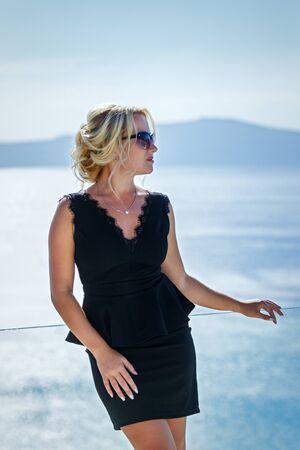 Beautiful woman in dress against the sea  of Santorini island, Greece