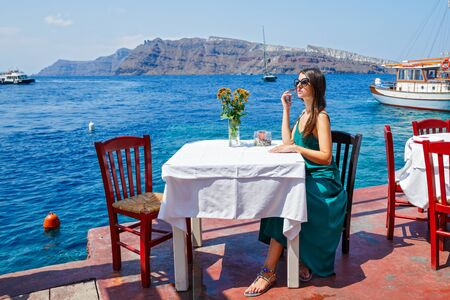Young woman in a dress sitting at a table beach restaurant on the beach