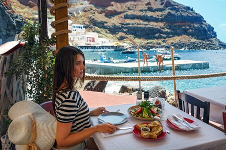 Young woman having dinner at a fish restaurant on the beach Stok Fotoğraf