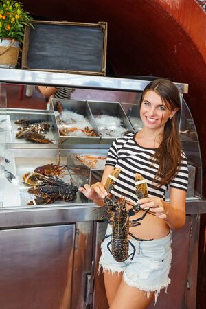 Young woman at the window of a fish shop chooses lobster