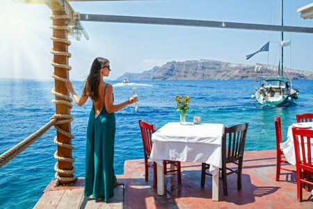 Young woman in a dress standing at a table beach restaurant on the beach