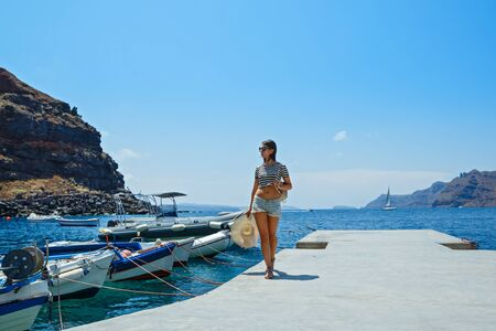 Young woman walking on the pier for yachts and boats