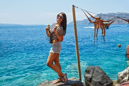 Young woman holds in hands of lobster, on the background of the sea and octopus on a rope Stockfoto