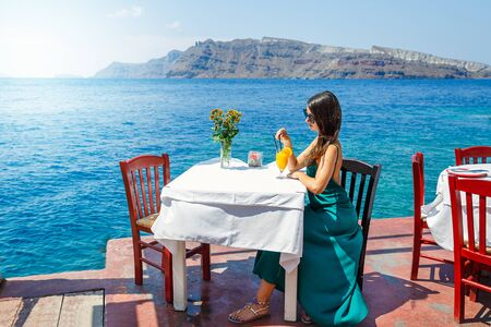 Young woman sitting at a restaurant table on the beach