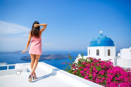 Young woman in a pink dress stands on the terrace and looks at the sea